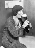 Woman drinking out of a big beer glass  - 104441606
