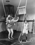 Female gymnast training with safety ropes with coach  - 104442046