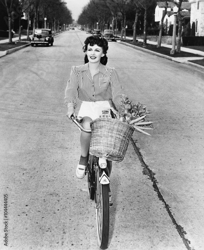 Young woman riding her bicycle with basket full of flowers and carrots  - 104444405