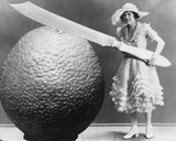 Woman with huge knife and piece of fruit  - 104445096