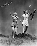 Two women running and playing with model airplanes  - 104446097