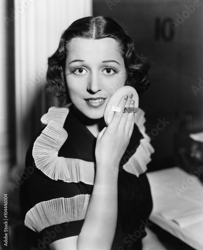 Portrait of a young woman applying powder to her face  - 104446004