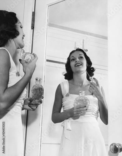 Woman applying perfume at mirror  - 104451003