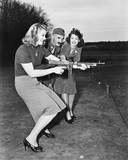 Two young women and a soldier trying out a machine gun  - 104453444