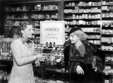 Two women in a drug store looking at each other  - 104453660