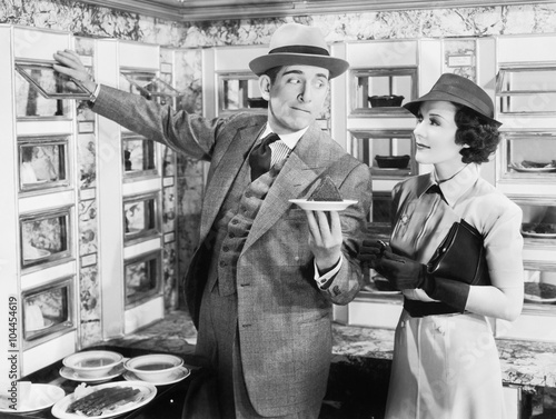 Man serving a dish to a woman in a Automat  - 104454619