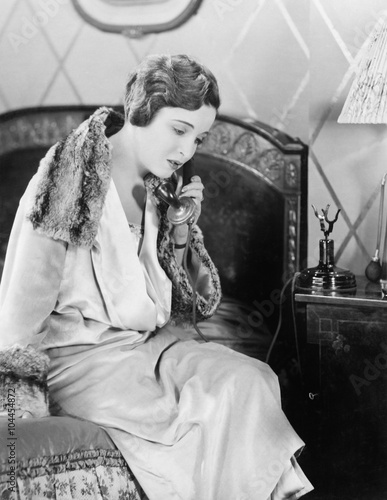 Young woman sitting on her bed in the bed room, speaking on the telephone