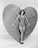 Woman surrounded by arrows on huge heart  - 104456270