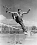 Male tennis player jumping over net  - 104456476