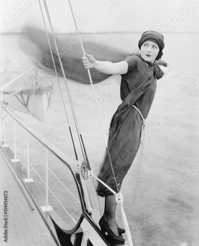 Woman leaning off boat into the wind  - 104456673