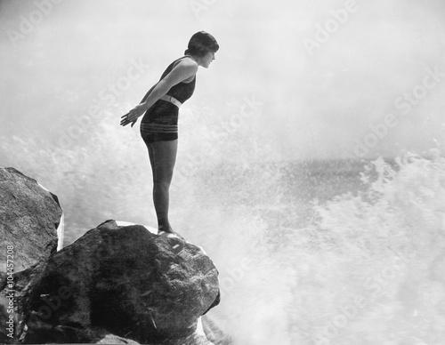 Female swimmer on rock above crashing surf  - 104457208