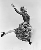 Woman in a flowing skirt leaping through the air  - 104459059
