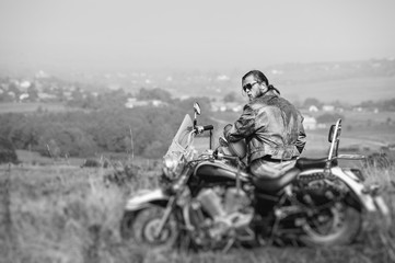 Brutal biker with beard wearing leather jacket and sunglasses sitting on his motorcycle on a sunny day, holding helmet. Horizontal picture. Rear view. Tilt shift lens blur effect. Black and white