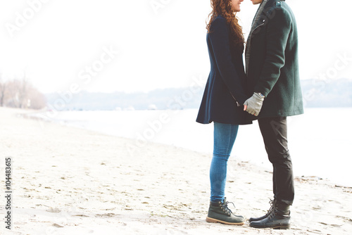 Cute young couple in love standing on the riverside