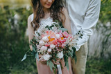 couple holding a bouquet of pink and white peonies and green