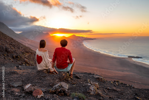 Poster Young couple enjoying beautiful sunset sitting together on the mountain with gre