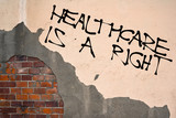 Handwritten graffiti Healthcare Is a Right sprayed on the wall, anarchist aesthetics