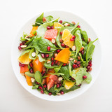 Fototapety Fresh salad with fruits and greens on white background top view. Healthy food.