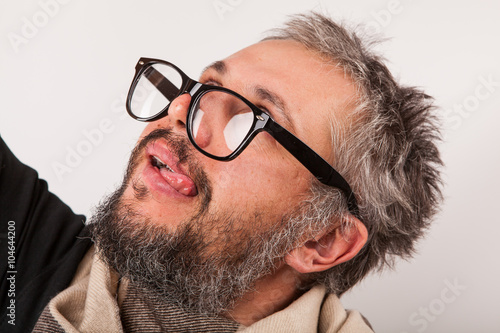 Crazy looking old man with grey beard nerd big glasses show tongue Canvas Print