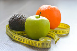 Apple, orange and avocado with measuring tape suggesting diet concept