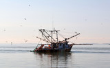 Commercial Fishing Boat/Commercial fishing boat enters the harbor at sunset.