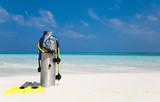 Taucherflasche mit Taucherbrille, Flossen und Atemregler am Strand - 104685845