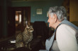 Tabby cat and elderly woman looking at each other
