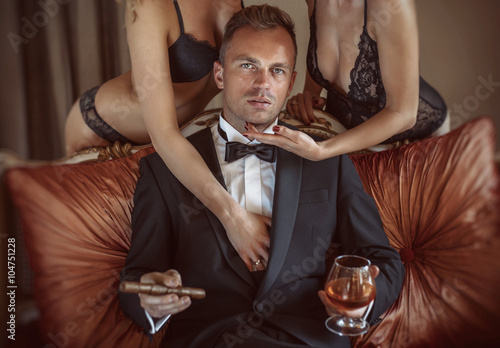Gentleman in the company of two sexy women Poster