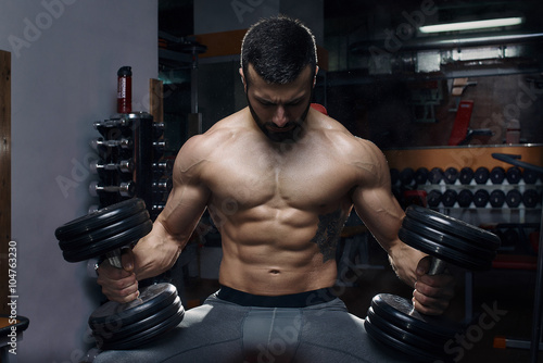 fototapeta na ścianę Men's physique athlete sitting with the barbells in the gym