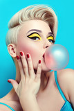Fototapety Fashionable girl with a stylish haircut inflates a chewing gum. The girl in the studio on a blue background. The girl's face with bright makeup and yellow with black shadows on the eyes.