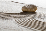 zen sand still-life -single stone on sinuous waves for concept of beauty spa or spirituality with inner peace