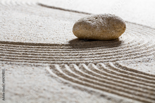 Foto op Plexiglas Stenen in het Zand zen sand still-life -single stone on sinuous waves for concept of beauty spa or spirituality with inner peace