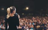 Donna con microfono su palco pubblico - 104820251
