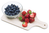 Isolated blueberries and strawberries on wooden cutting board.