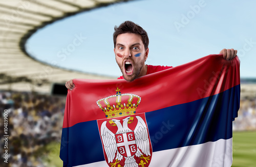 Fan holding the flag of Serbia in the stadium