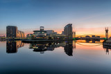 Orange sunrise at Salford Quays with blue sky and clear reflections in canal. - 104839626