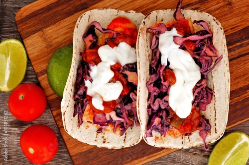 Vászonkép Two spicy fish tacos with red cabbage lime slaw, salsa and sour cream, downward