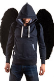 young man in gray jacket with hood thrown over his head and jeans standing with her hands on back and black wings