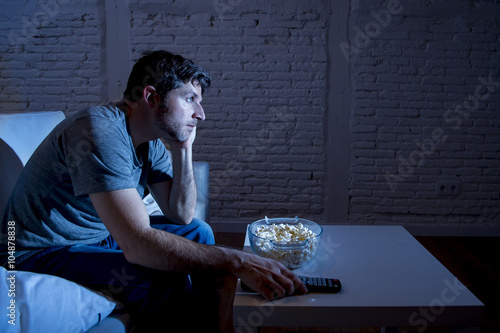 Plagát television addict man sitting on sofa watching TV eating popcorn using remote co