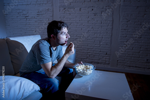 Plagát young television addict man sitting on home sofa watching TV and eating popcorn