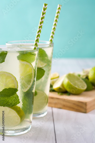 Summer drink. Fresh mojito with lime and mint. Blue background Plakat