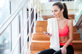 Fototapety Happy charming sportswoman listening to music from smartphone in gym