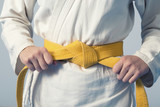 Fototapety Hands tightening yellow belt on a teenage dressed in kimono for martial arts