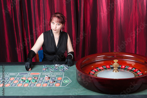 Plakat sexy lass wearing  black gloves and black dress plays in a casino