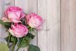 Obrazy na płótnie, fototapety, zdjęcia, fotoobrazy drukowane : Three pink roses on a wooden platform, top view.