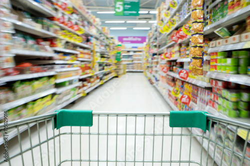 Poster Shopping in supermarket shopping cart view with motion blur