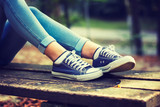 Young woman in jeans and blue sneakers on a bench in the park