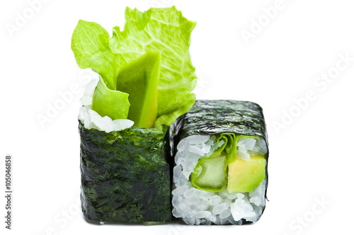 Fototapeta Two sushi maki rolls with avocado, cucumber and green salad leaf on white background