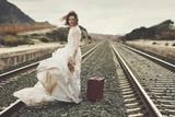 novia pensativa con una maleta roja en las vías del tren