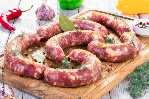 obraz lub plakat raw sausages prepared for grill with chilli pepper, garlic, close-up